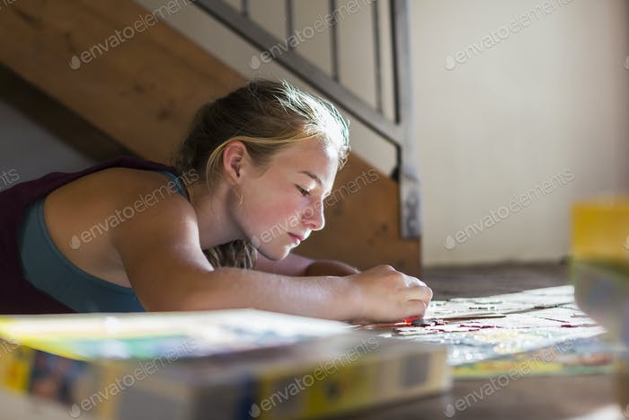 13 year old girl lying ion floor, doing jigsaw puzzle