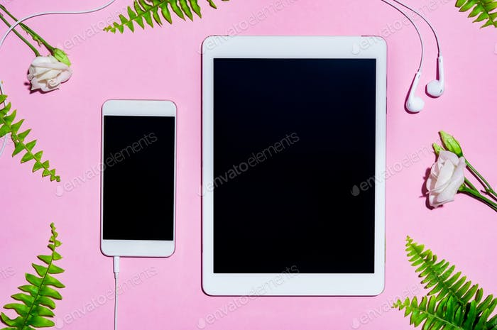 Mobile and digital tablet on pink