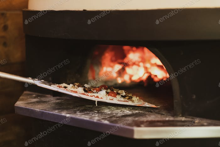 Close up of pizza in a wood-fired oven in a restaurant.