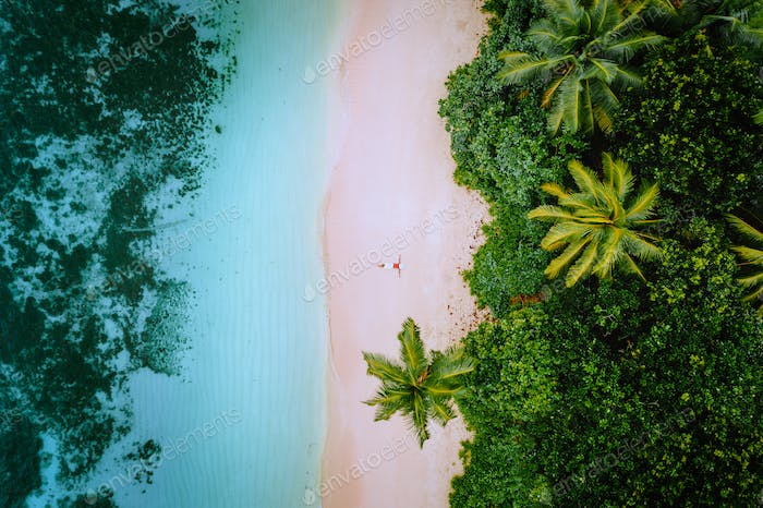 Aerial view of a young woman relaxing on the tropical paradise sandy beach surrounded by palm trees
