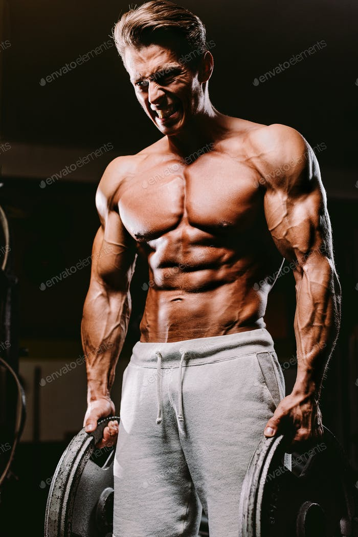 Muscular fit man pumping muscles.
