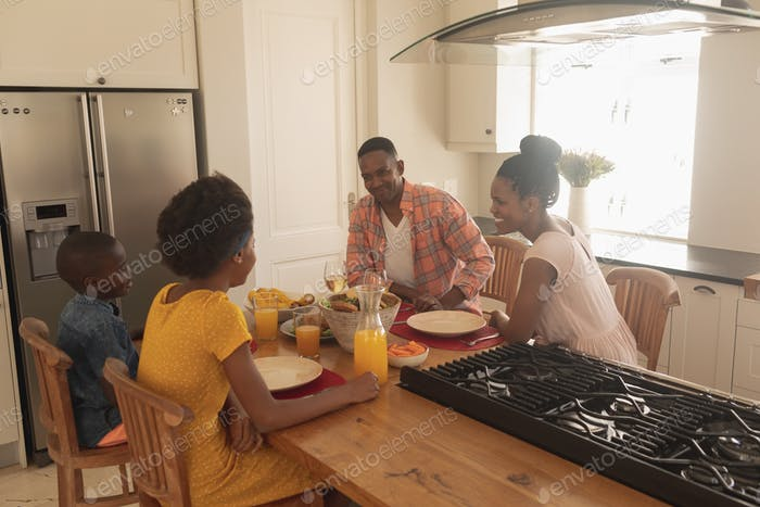 Side view of happy African American family having food at dining table in a comfortable home