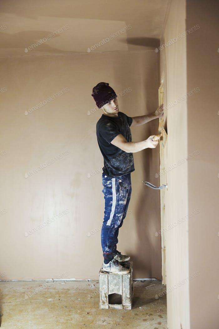 Ein Arbeiter, ein Elektriker, der auf einer Hausbaustelle arbeitet.