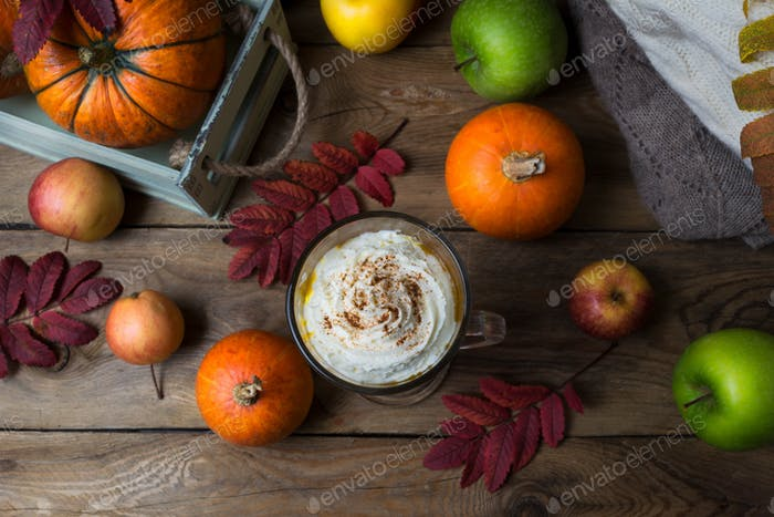 Pumpkin spice coffee latte with cream and cocoa, top view