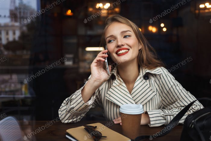 Pretty smiling girl in striped trench coat talking on cellphone