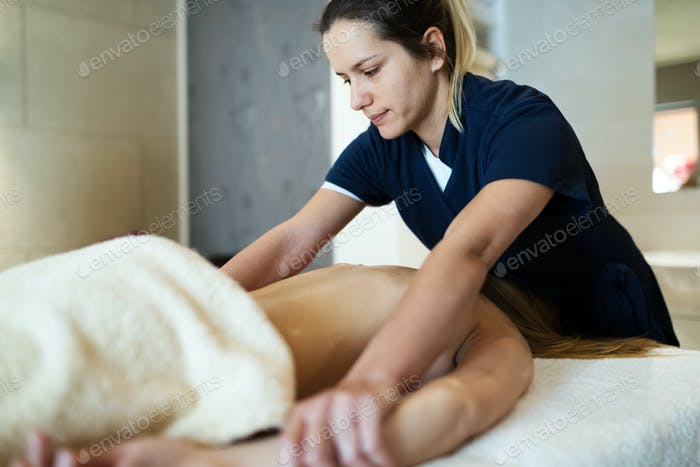 Professional masseur working on client