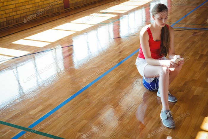Young woman using mobile phone in basketball court
