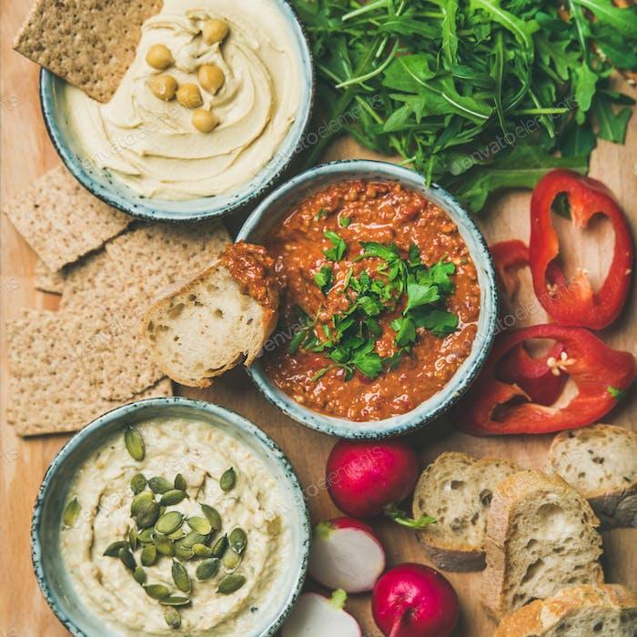 Flat-lay of Vegetarian dips hummus, babaganush, muhammara, square crop