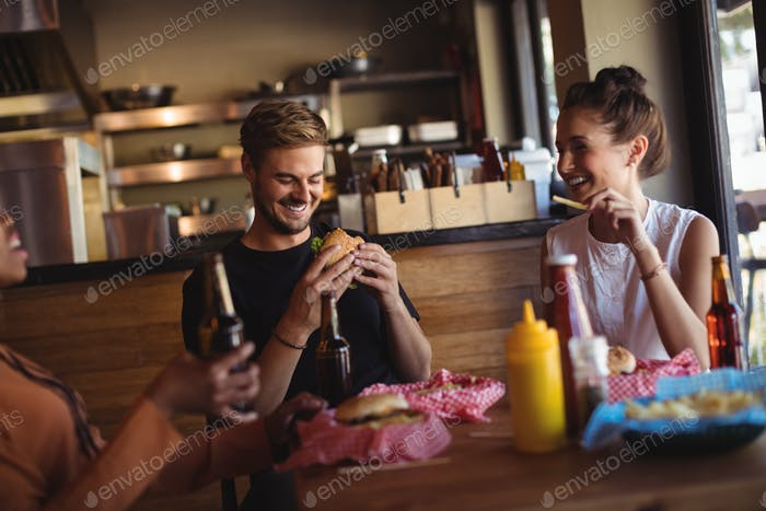 Happy friends interacting while having meal and beer