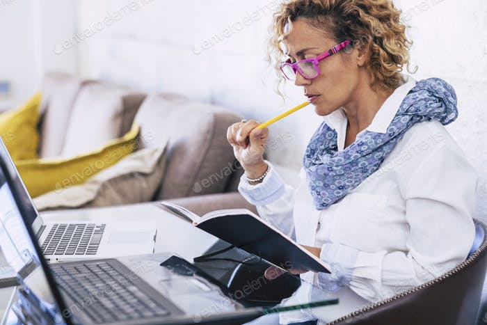 Adult woman at home working with modern technology laptop and old paper documents