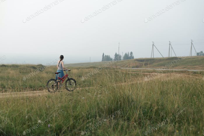 white caucasian young woman going with cycle, on village road