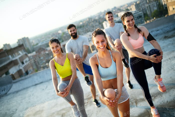 Fitness, friendship, sport and healthy lifestyle concept - group of happy friends exercising