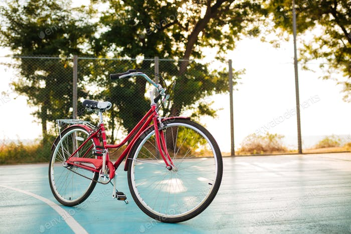 Close up photo of  red classic bicycle standing on basketball court in park