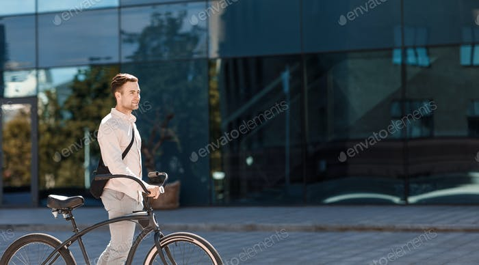 Transport, lifestyle and activity. Guy in formal clothes goes with bike