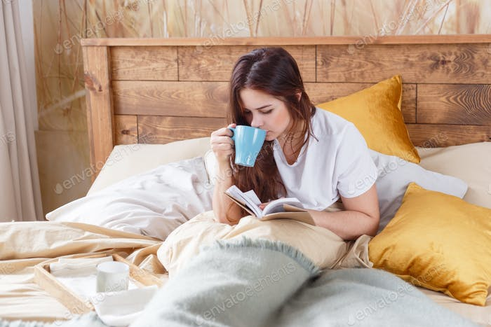 Cute girl on a comfortable chair with tea ,reading a book, the concept of comfort and hipster.