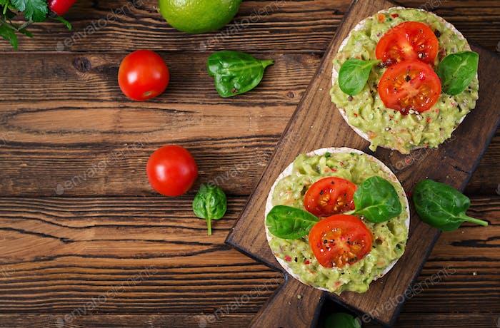 Healthy breakfast. Sandwich crisp bread with guacamole and tomatoes