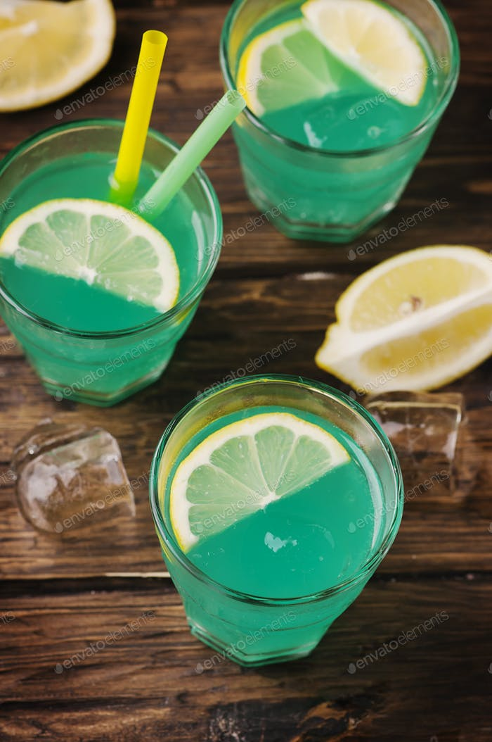 Green cocktail with lemon and ice on the wooden table