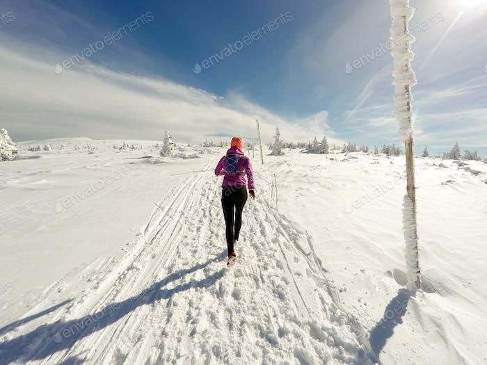 Mujer corriendo en el sendero de invierno, Nieve y montañas blancas