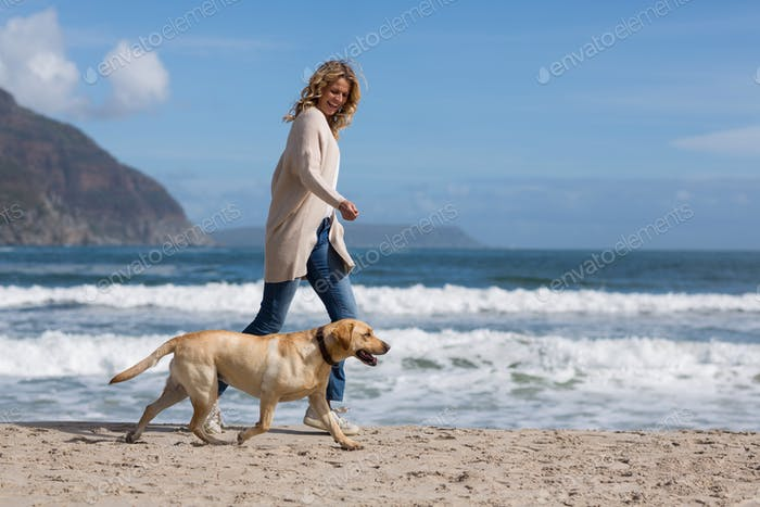 Woman walking with her dog on the beac