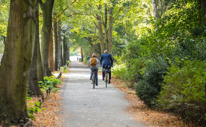 Tiergarten city park in Berlin, Germany. View of a mature couple riding bicycles