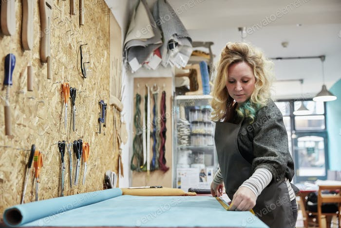 A woman preparing, measuring and cutting upholstery fabric on a workbench.