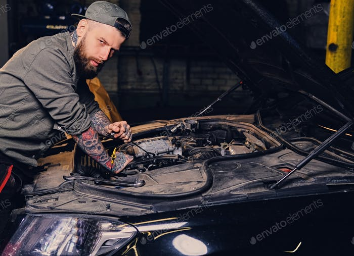 Bearded tattooed mechanics near car in a garage.