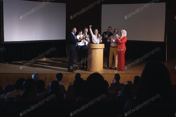Businesswoman standing at the stage of the auditorium with colleagues in front of audience