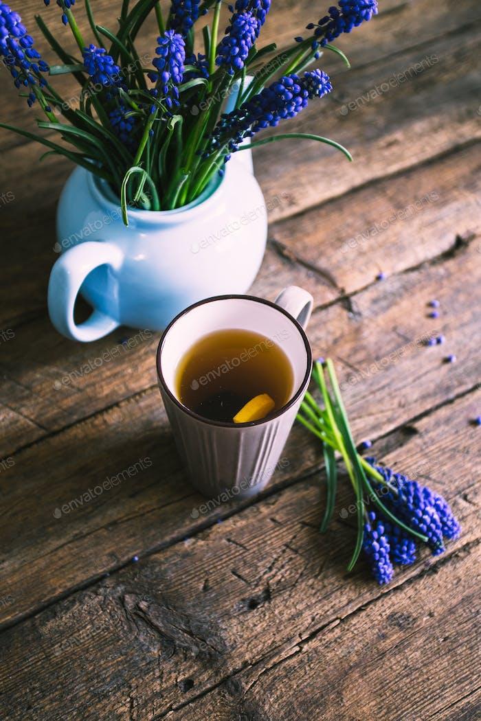 Blaue Blüten in einer Teekanne mit einer Tasse Tee auf hölzernem Hintergrund. Vintage-Design