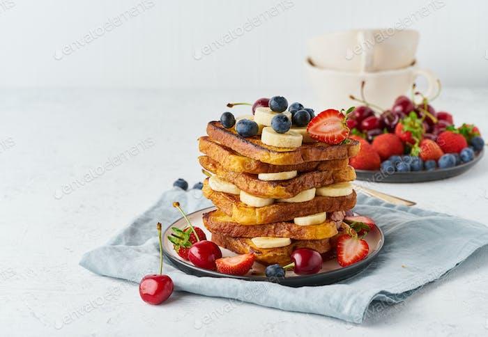 Französisch Toast mit Beeren und Banane, Brioche-Frühstück, weißem Hintergrund, Nahaufnahme