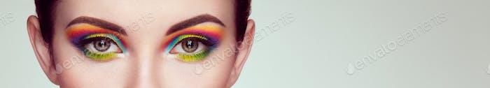 Weibliches Auge mit Regenbogen-Make-up