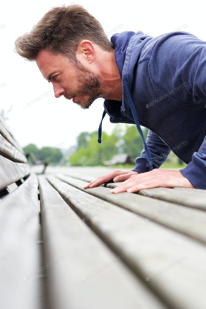 Attractive male doing pushup on bench