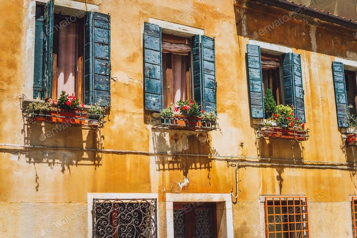 Venice old yellow facade of house with wood windows on the street in Venice Italy