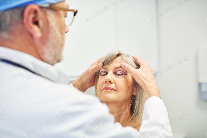 Kosmetik Chirurg hält erwachsene Frau Kopf und Diagnose