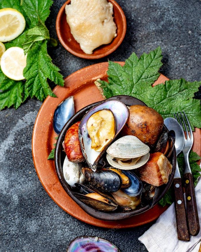 Kuranto Kuranto. Verschiedene Meeresfrüchte und Fleisch in einer Grube auf den Kohlen unter dem Boden  gekocht