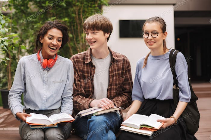 Group of students sitting on bench with books and happily looking in camera