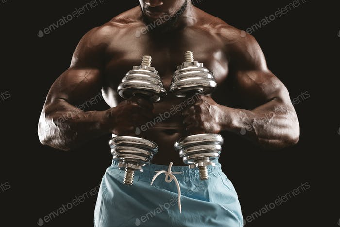 Strong athletic body of african bodybuilder holding dumbbells