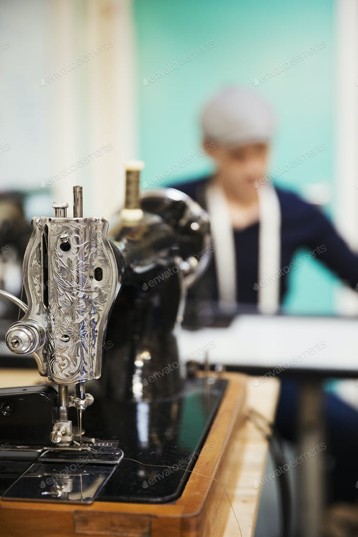 A retro style traditional sewing machine with chased metalwork, and a tailor working in the
