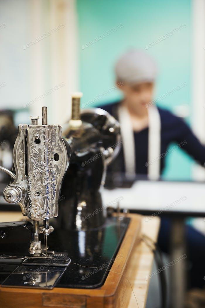 Eine traditionelle Retro-Stil-Nähmaschine mit gejagter Metallarbeit und ein Schneider, der in der