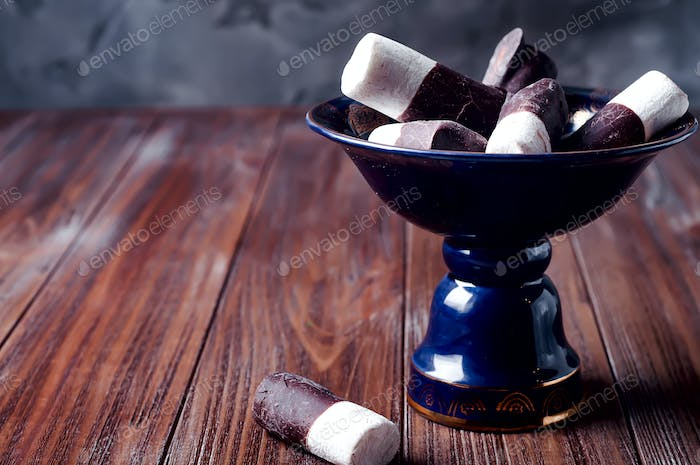 marshmallows and chocolate into a bowl on  dark background