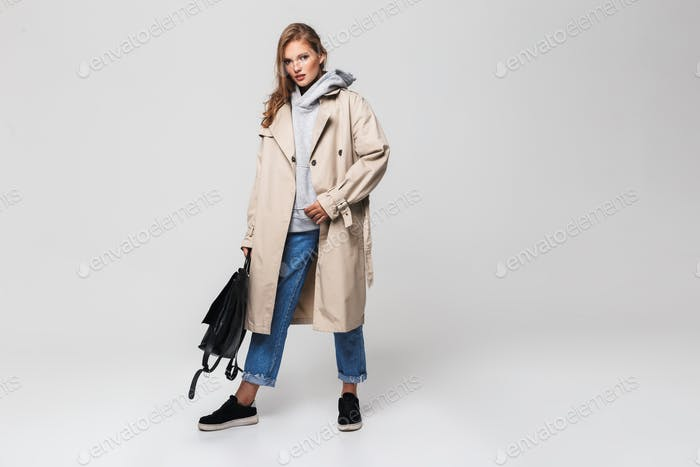 Young gorgeous woman in trench coat and jeans holding black backpack in hand