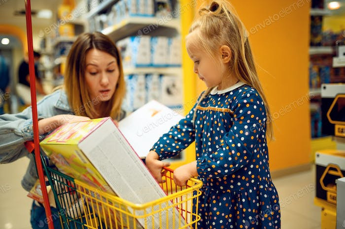 Mother and pretty little baby buying toys in store