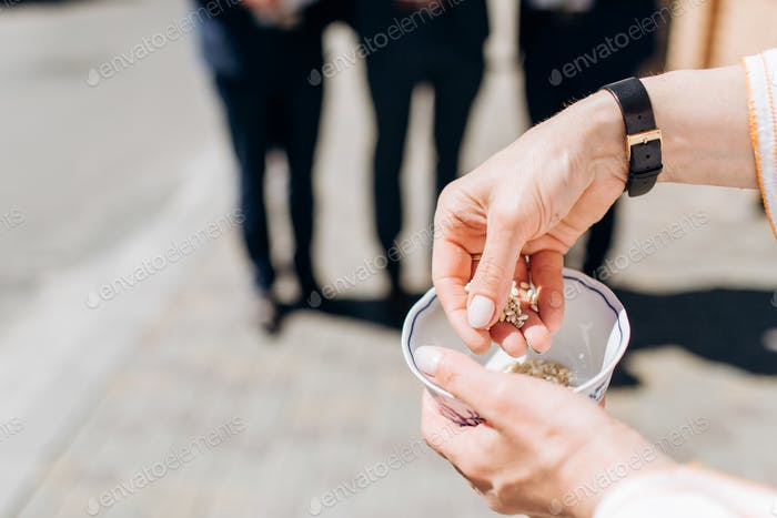 Closeup of man holding rice bowl to throw at married couple