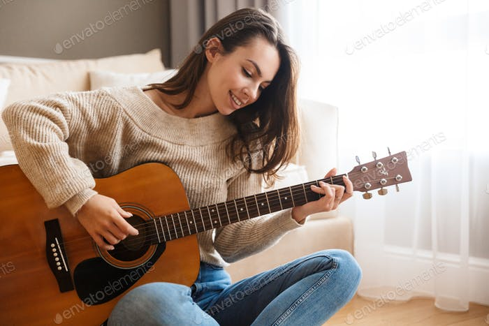 Image of happy beautiful woman playing guitar and composing song