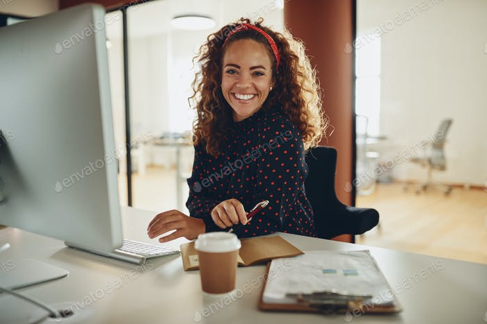 Smiling businesswoman sitting at her office workstation going over paperwork