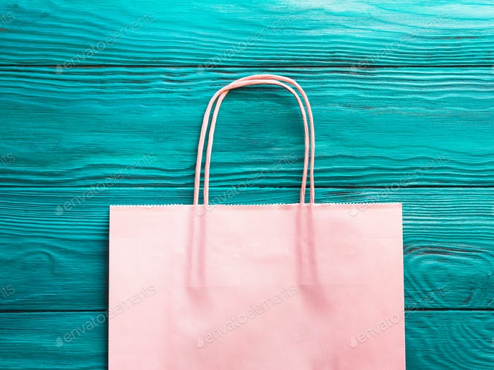 Pink shopping bag on green background