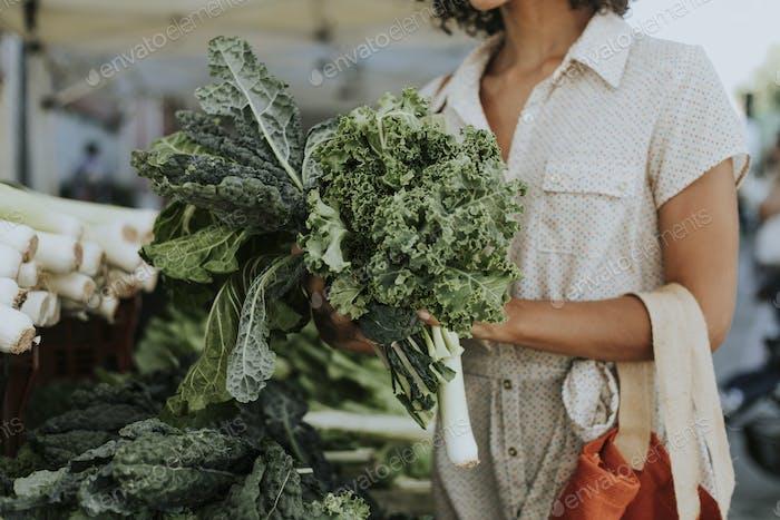 Schöne Frau kaufen Grünkohl auf einem Bauernmarkt