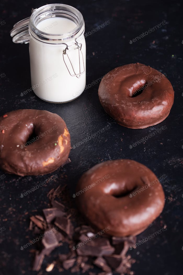 Chocolate donuts near bottle of milk and chocolate crumbs