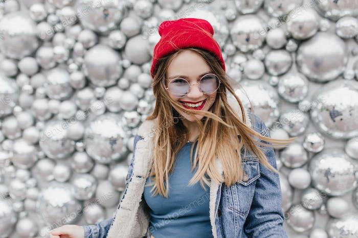 Chica europea encantadora en lindo sombrero rojo posando con sonrisa feliz. Foto de la mujer rubia bonita en la den