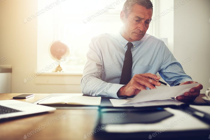 Mature lawyer reading through documents at his office desk