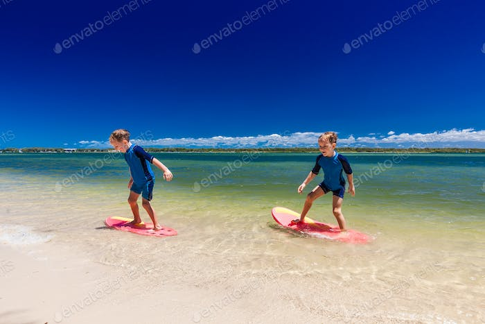 Surfer twin brothers have fun on beach learning to surf